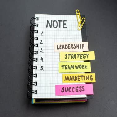 front-view-motivation-business-notes-with-notepad-dark-background