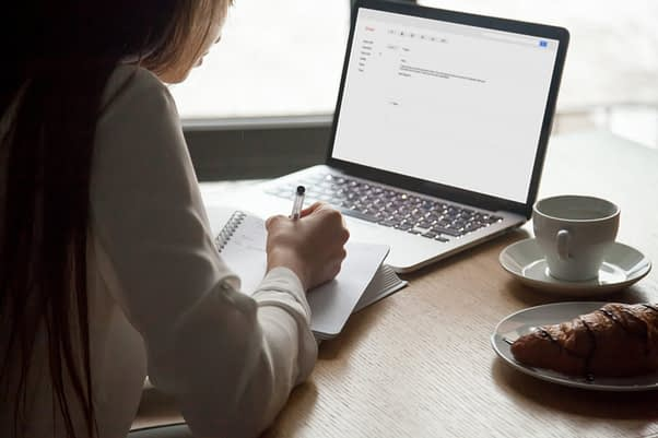 Woman making notes reading email letter on laptop in cafe