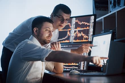 Team of stockbrokers are having a conversation in a dark office with display screens. Analyzing data, graphs and reports for investment purposes. Creative teamwork traders