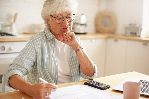 Candid shot of serious Caucasian retired woman in spectacles calculating expenses, trying to save money for expensive purchase, paying domestic bills online using electronic gadget at kitchen table