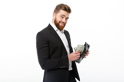 Happy bearded business man holding purse with money