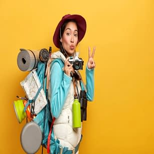 pretty-active-backpacker-makes-victory-gesture-keeps-lips-rounded-holds-retro-camera-stands-with-travelbag-takes-photos-during-trip-isolated-yellow-background